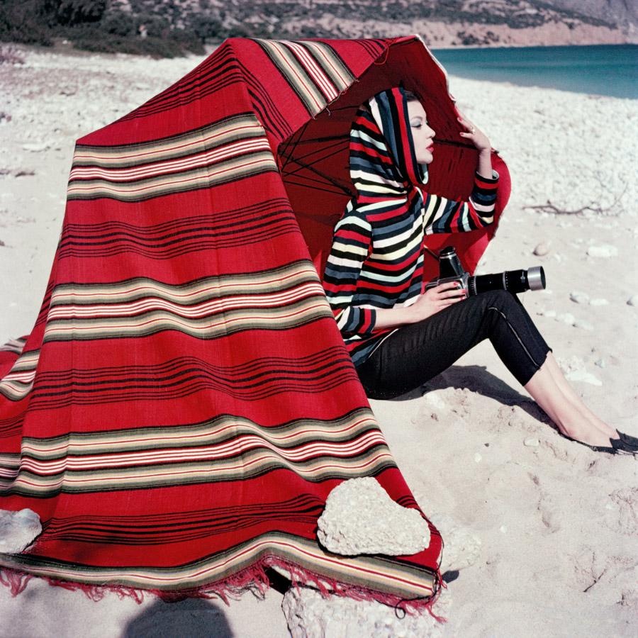 au bord de mer, Barbara Mullen, vêtue d'un sweat à capuche à rayures Christian Dior, tient un appareil photo argentique en main.