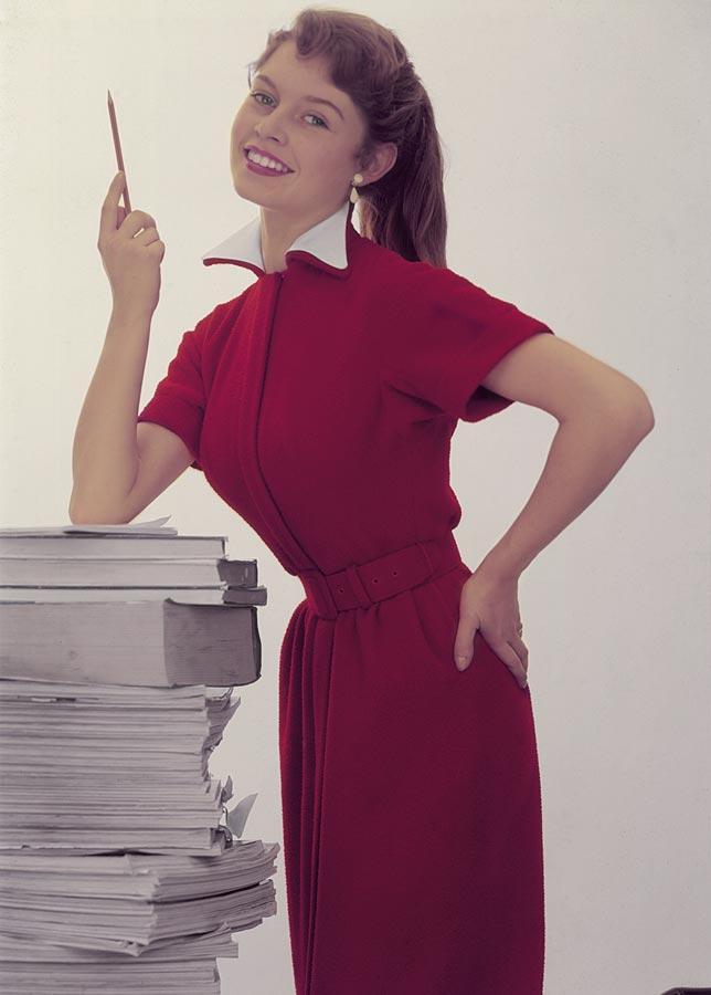 Brigitte Bardot toute jeune et toute vetûe de rouge, en secrétaire, s'appuie sur une pile de magazines stylo en main.