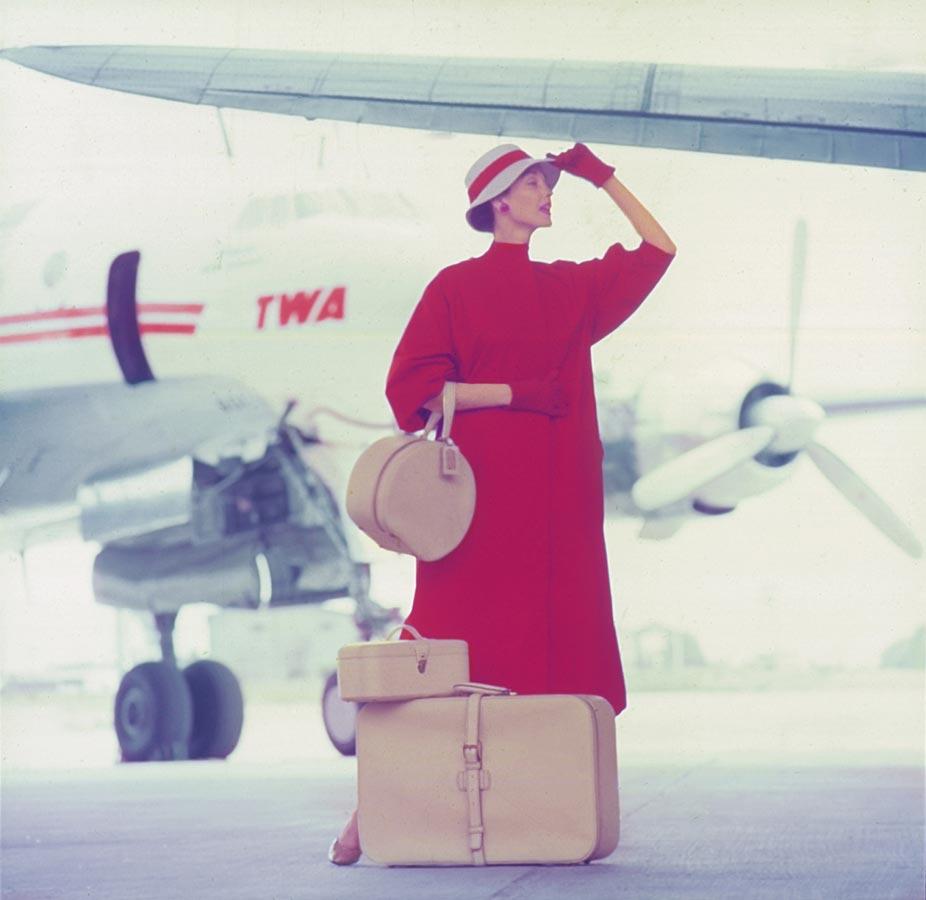 Femme vêtue de rouge avec des bagages aériens davant un avion de la compagnie américaine TWA,
