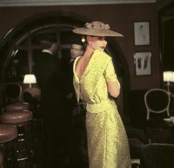 Photographie inédite prise chez Maxim's, femme portant un ensemble jaune décolleté dans le dos de Lanvin Castillo.