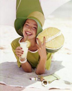 Dolores Hawkins buvant à la paille un cocktail. Elle porte un chapeau vert et un sac en forme de citron.