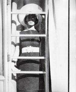 Femme deriière une fenêtre dont les barreaux font de l'ombre.