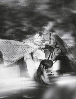 Femme et fillette au volant d'une voiture décapotable. Foulard à pois au vent.
