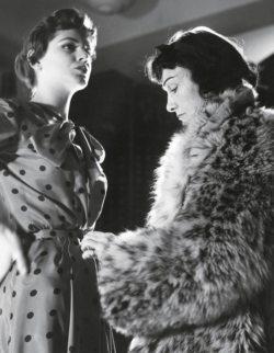 Gabrielle Chanel en manteau de fourrure et son mannequin Vera Valdez dans une robe à pois lors d'une séance d'essayage