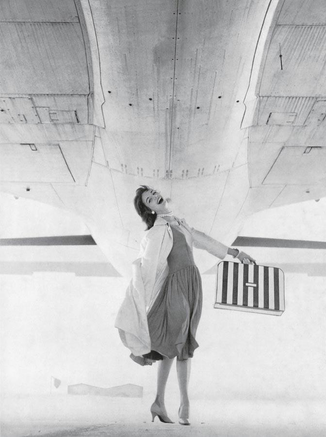 Femme dans une robe Givengy sous un avion potant ue valise rayée