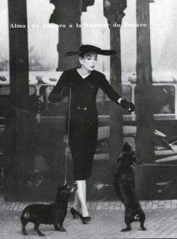 Mannequin portant un tailleur en lainage noir de. Givenchy ; elle tient un chien en laisse et donne un sucre à un autre teckel.