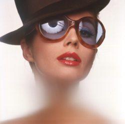 La mannequin islandaise Gudrun Bjanadottir-Bergese porte des lunettes de soleil et un chapeau masculin, les lèvres maquillées de rouge,