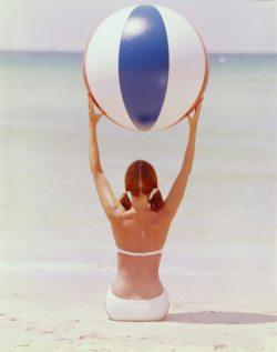 Le mannequin Dolores Hawkins vue de dos, en maillot 2-pèces portant un ballon de plage face à la mer
