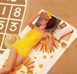 La mannequin Pia Rossilli prend un bain de soleil : allongée en maillot de bain jaune, lunette de soleil en main, elle lit un livre de poche d'Agatha Christie,