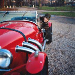 Un homme (le couturier Pierre Cardin) au volant d'une luxueuse voiture de course décapotable rouge Mercedes-Benz SSK