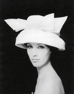 une femme porte un grand chapeau bllanc